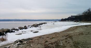 Beach view of partially frozen Hudson River