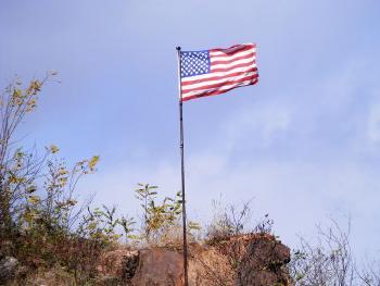 Flag atop rock outcropping near Rt 9/9A split