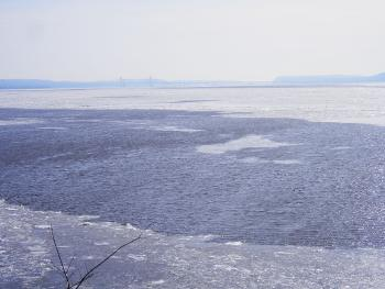 Southern somewhat frozen Hudson River view from Teller's Point at Croton Point Park. New Tap Zee bridge in foggy distance.